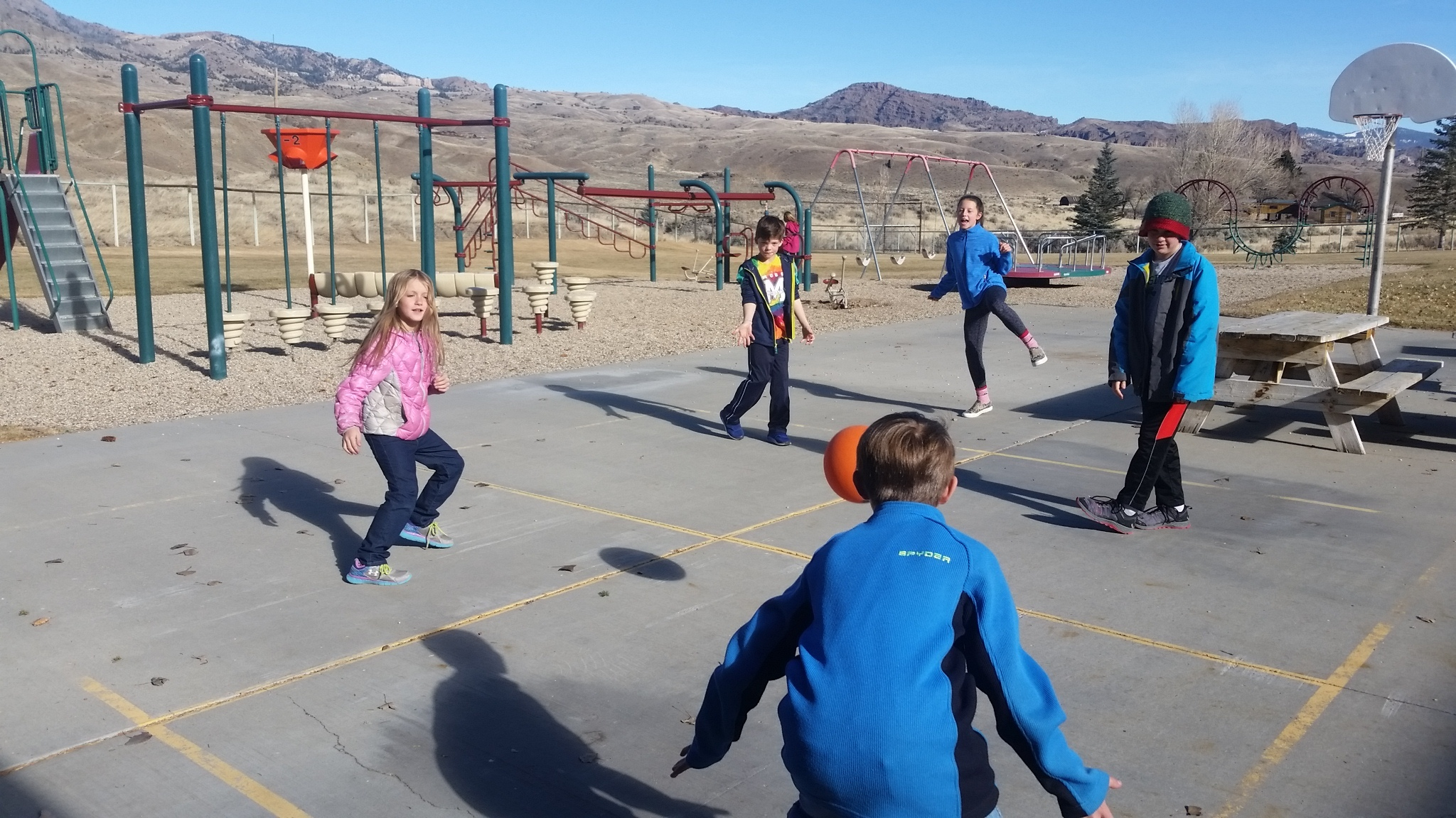 Students play four square at school playground.